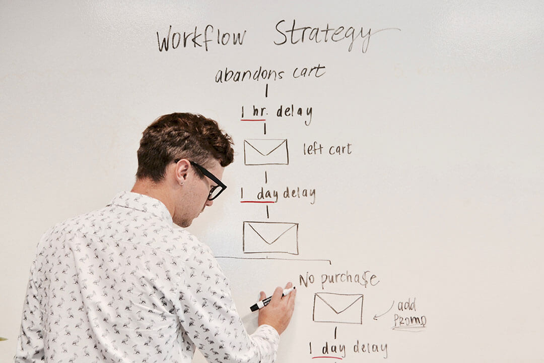 Person writing schematic online campaign strategy on whiteboard