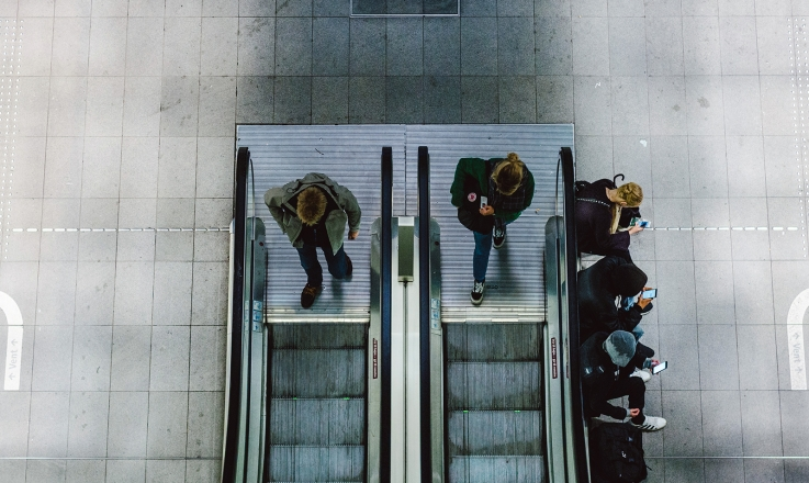 People on escalator using smartphones